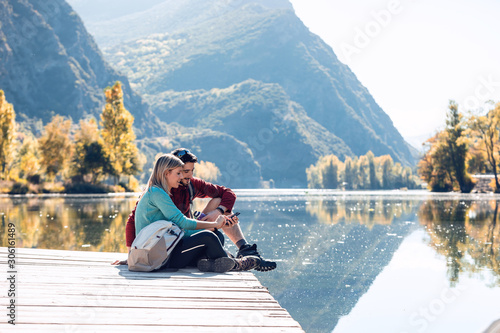 Tela Two travel hikers using mobile phone while sitting in front of the lake in mountain