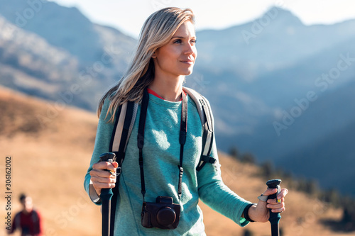 Fototapeta Pretty young woman traveler with backpack looking to the side while walking on mountain. obraz