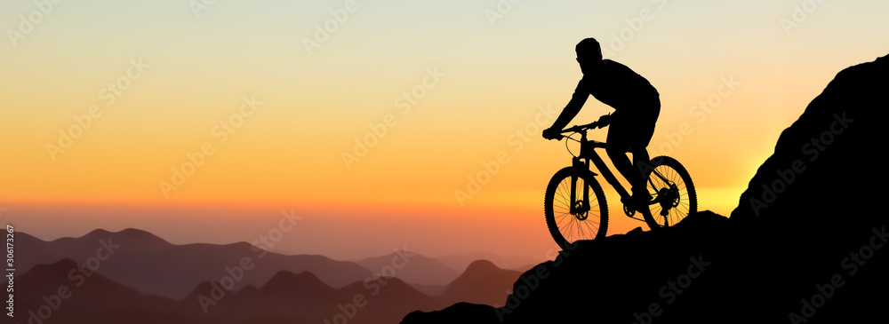 Fototapeta Conquering mountain peaks by cyclist in shorts and jersey on a modern carbon hardtail bike with an air suspension fork . Beautiful view from the mountain. Panoramic view for banner.