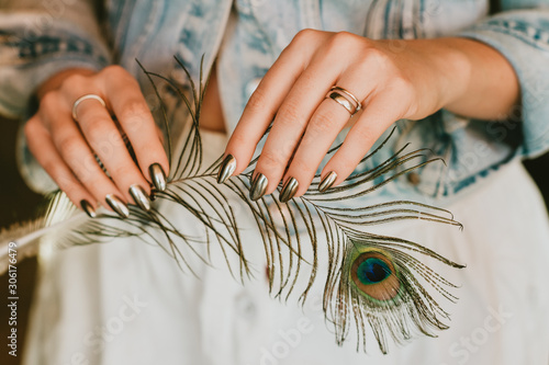 Vászonkép Stylish trendy female mirror manicure, metal nail art, holding peacock feather