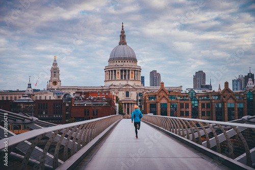 Photo  Young active man running at Millennium Footbridge over the Thames, St Paul's Cat