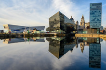 Modern Office Buildings And The Liver Building Along With Their Reflections In The Deep Blue Water Of Canning Dock On A Sunny Day