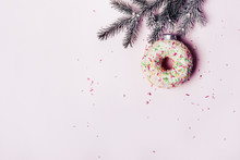 Christmas Creative Background. Christmas Ball Made Of Decorated Donut Hanging On Christmas Tree Branch