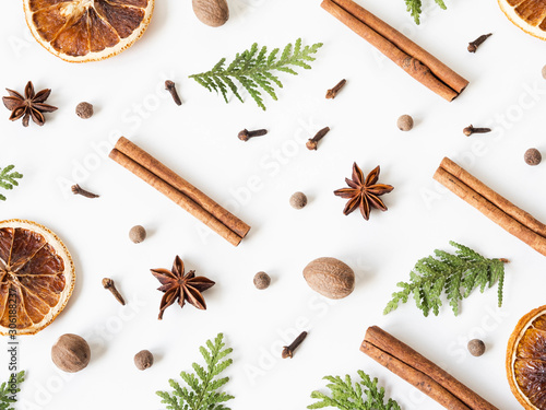 Obraz Flat lay creative Christmas vibrant composition with fir branches, Christmas decorations and spices on a white background. Top view - fototapety do salonu