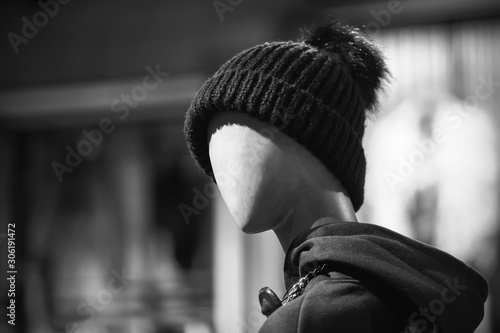 Fotografija  A black-and-white image of a sinister, frightening, faceless mannequin standing in a clothing store wearing a hat and hoodie