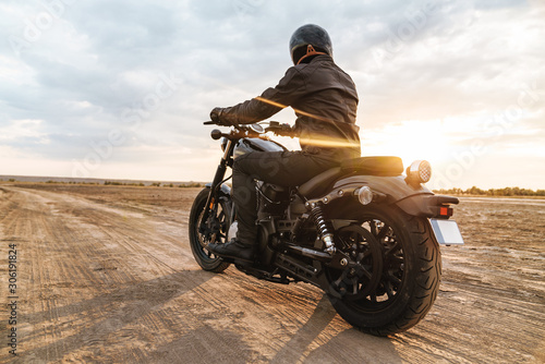 Foto Handsome young man biker on bike outdoors