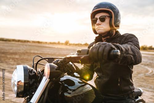 Fotografía  Young man biker on bike outdoors at the desert field.