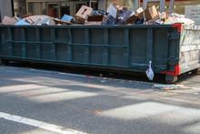 Long Overflowing Metal Dumpste...