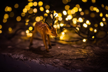 Cute adorable baby deer in a decorated  Christmas setting with Christmas lights.