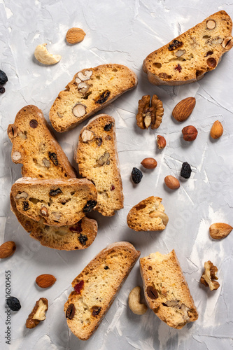 Fotografija Tasty traditional Italian homemade biscotti or cantuccini cookies with hazelnuts, almonds, raisins and walnuts on a light gray background