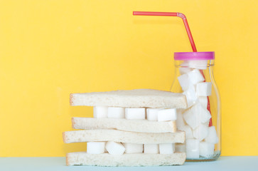 Sandwich with sugar and glass full of sugar cubes .Too much sugar and unhealthy food concept.