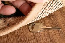 A Man Raises A Key Hidden Under A Mat
