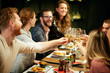 canvas print picture - Best friends sitting in restaurant for dinner and making a toast with white wine. On table is food.
