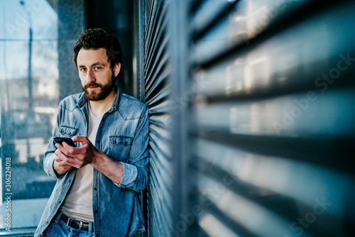 Valokuvatapetti Handsome caucasian millennial male standing outdoors with smartphone share publication in blog via 4G connection, hipster guy  in casual wear using mobile phone for chatting spend free time on street