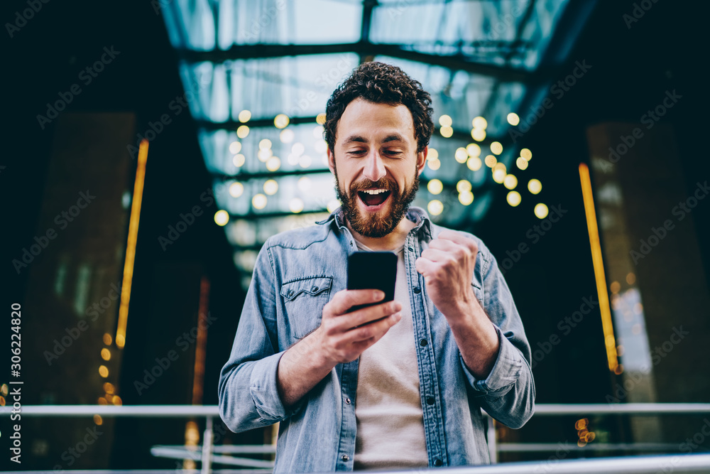 Fototapeta Emotional caucasian hipster guy excited with result of match victory watching video online on smartphone and 4G connection, happy millennial male overjoyed with get new free app for mobile phone .