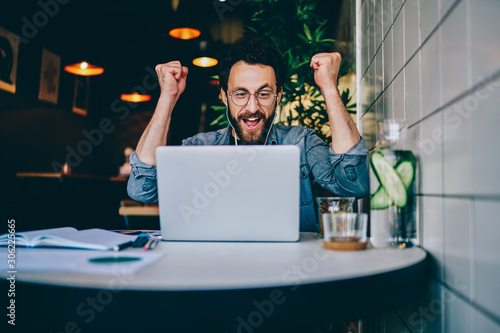 Fényképezés Overjoyed hipster guy in earphones cheers for team watching match on laptop computer during free time in cafe interior, amazed emotional male freelancer celebrating achievement and completing project