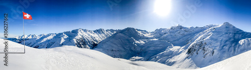 swiss alps mountain range in winter with blue sky and switzerland national flag