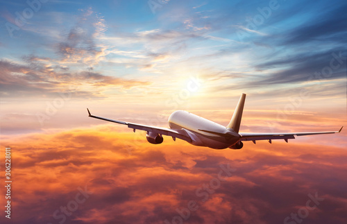 Passengers commercial airplane flying above clouds - fototapety na wymiar