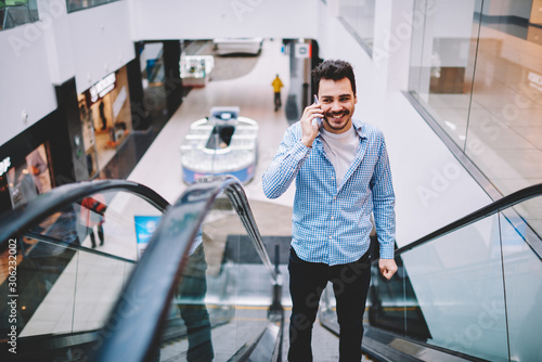 Fototapety, obrazy: Cheerful man dressed in stylish casual wear escalating upstairs to second floor on publicity area with shops calling to friend during leisure time, happy man laughing during smartphone conversation