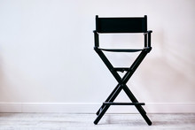 Black Director's Chair Against A White Wall