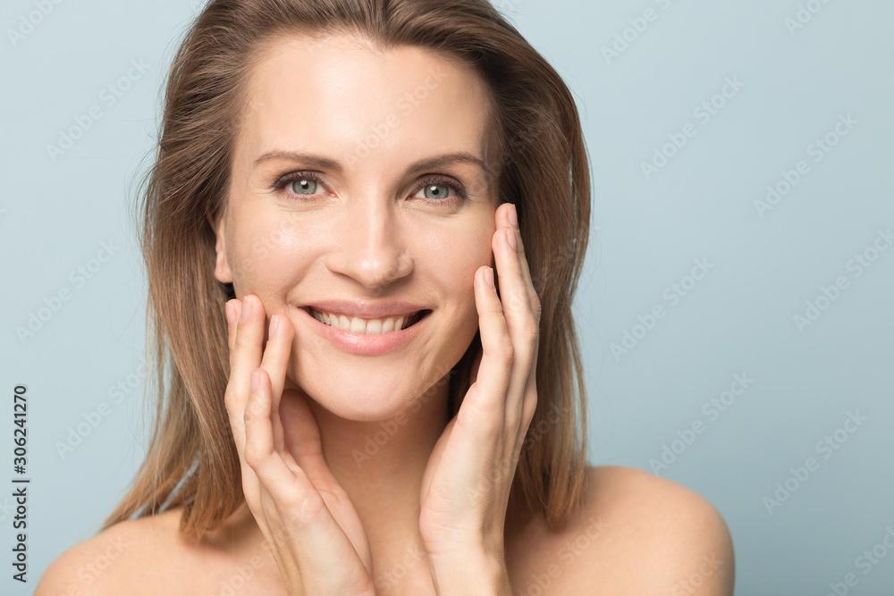 Fototapeta Head shot portrait smiling woman touching perfect smooth face skin