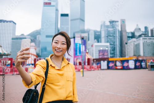 Valokuva  Half length portrait of cheerful female influencer clicking selfie pictures for