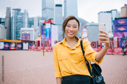 Valokuvatapetti Half length portrait of positive female influencer clicking selfie pictures for