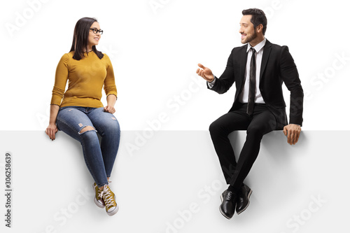 Obraz Businessman talking to a young female and sitting on a panel - fototapety do salonu