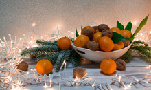 Healthy Mandarin And Walnuts  With  Christmas Tree And Gold Ribbon With Christmas Lights