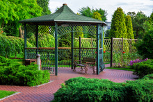 An Iron Gazebo With Shingles And A Park Bench With Bushes And Trees, A Lantern And An Urn By The Canopy On A Summer Day.