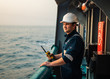 canvas print picture - Marine Deck Officer or Chief mate on deck of offshore vessel or ship , wearing PPE personal protective equipment - helmet, coverall. He holds VHF walkie-talkie radio in hands.