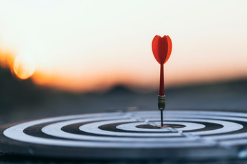 Close up red dart arrow hitting target center dartboard on sunset background. Business targeting and focus concept