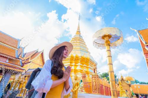 Photo A young woman praying at Wat Phra That Doi Suthep, a famous tourist attraction a