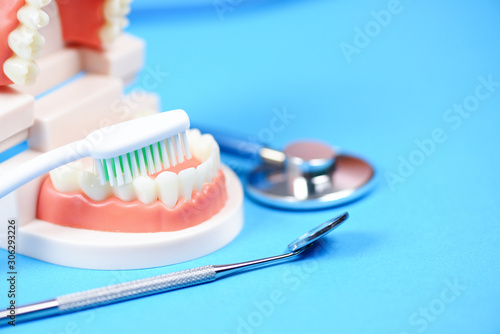 Fototapeta Dental care concept - dentist tools with dentures dentistry instruments and dental hygiene and equipment checkup with teeth model and mouth mirror oral health obraz