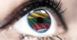 Woman blue eye in close up with the flag of Lithuania in iris with wind motion. video concept