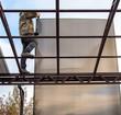 A worker mounts a metal canopy