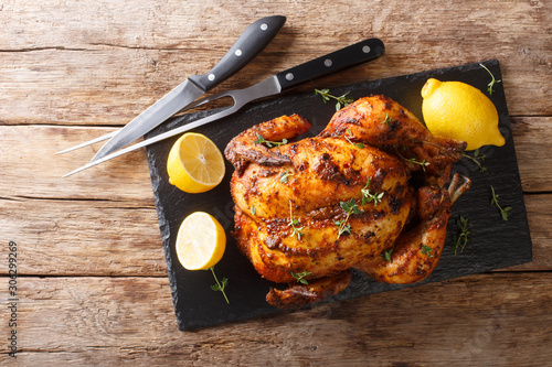 Fototapeta Traditional rotisserie chicken served with lemon closeup on a slate board on a table. Horizontal top view obraz