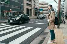 Pretty Asian Chinese Woman Traveler Walking In City Osaka Waiting For Traffic Lights To Cross Busy Road With Cars Driving By. Full Length Girl With Bag Standing On Street And Ready To Pass Pedestrian