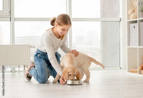 Obraz Happy girl next to eating puppy - fototapety do salonu