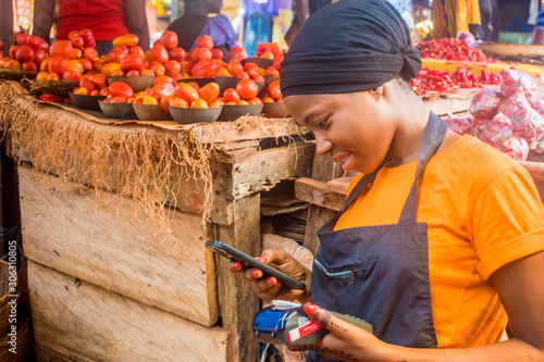 Fotomural young african woman selling in a local african market holding a mobile point of