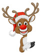 Christmas reindeer in a Santa hat cartoon character peeking around a sign and pointing at it