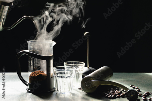 Tuinposter koffiebar The steam from a pot, Brewing method French press coffee maker on the old wood table and black background, Warm drinks make good healthy, Easy to make at home, Selective focus.