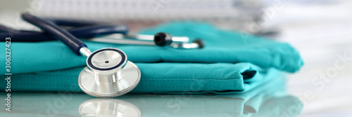 Medical stethoscope head lying on green doctor uniform Obraz na płótnie