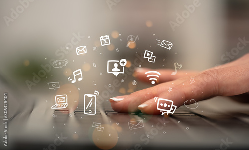 Obraz Business woman hand typing on keyboard with drawn application icons around - fototapety do salonu