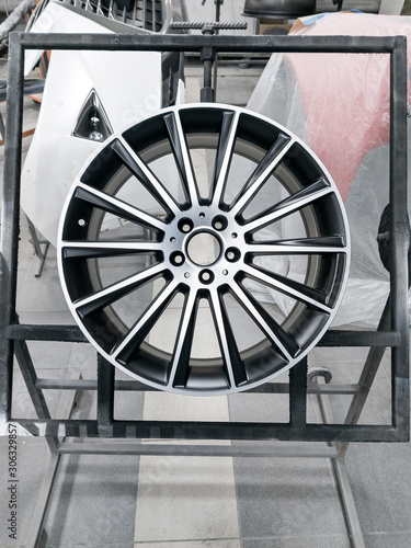 A two colored black and silver painted aluminum alloy wheel is mounted on a special frame during drying in a chamber in a vehicle body repair workshop Canvas Print