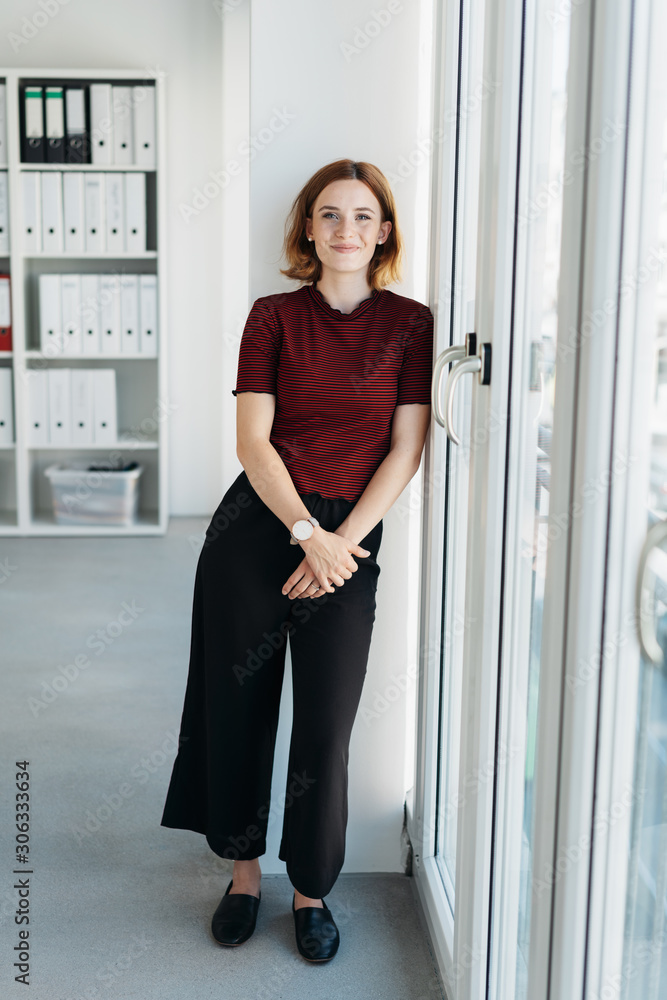 Fototapeta Trendy young businesswoman standing in the office