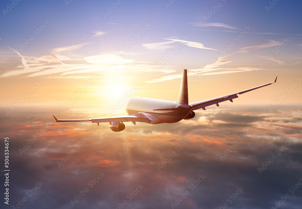 Pasażerski samolot handlowy latający nad chmury w świetle słońca. Pojęcie szybkiej podróży, wakacji i biznesu. <span>plik: #306334675 | autor: Jag_cz</span>