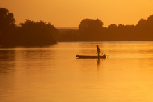 Silhouette Of The Fisherman On The Boat During Sunset On The Soderica Lake, Croatia