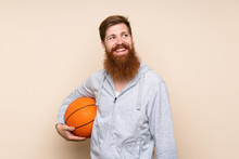Redhead Man With Long Beard Over Isolated Background With Ball Of Basketball