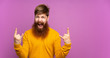 canvas print picture - Redhead man with long beard over isolated purple background making rock gesture